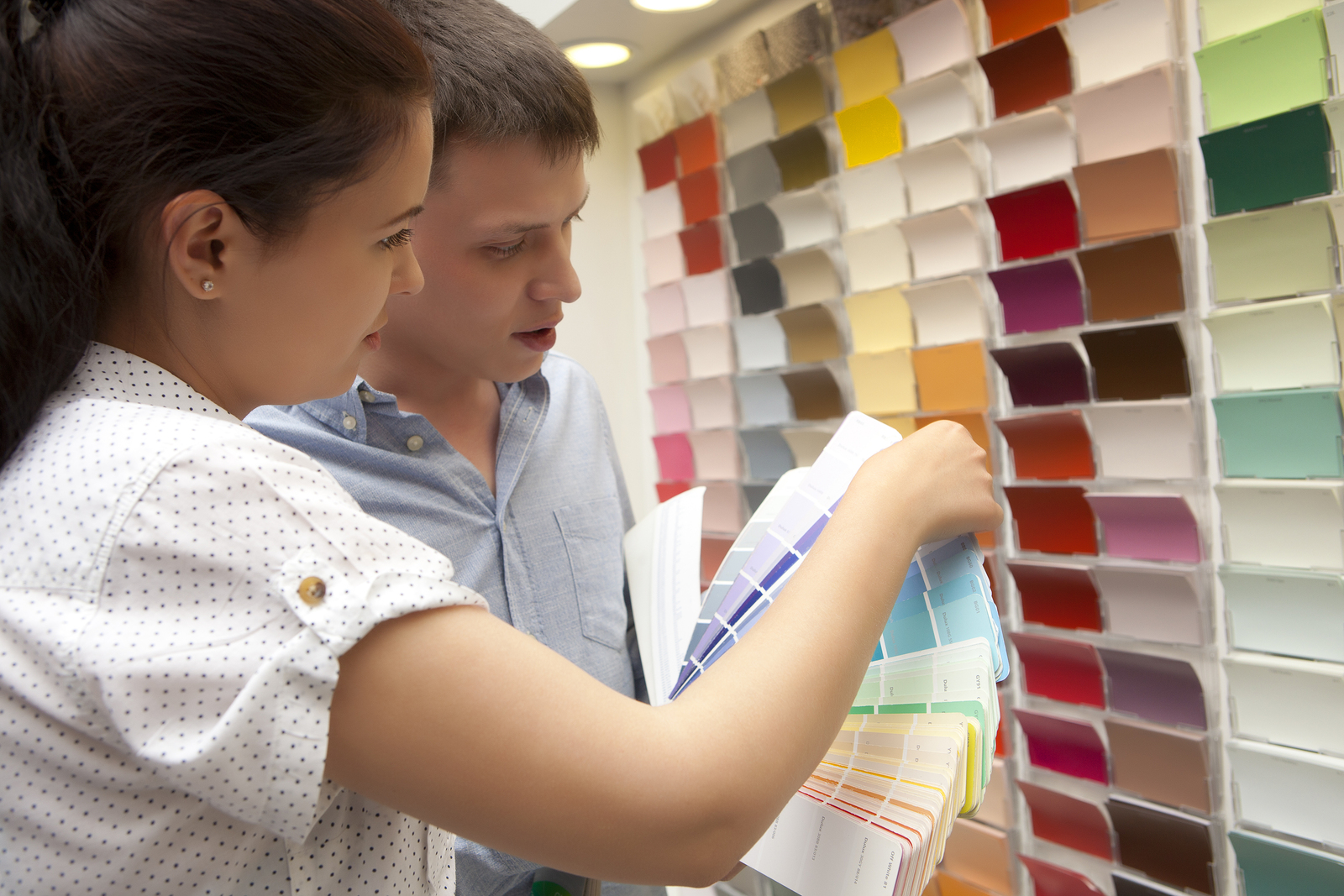 Couple select paint color and look matching samples at household